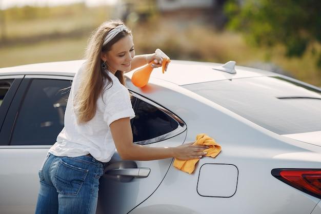 La donna elegante pulisce la macchina con uno straccio