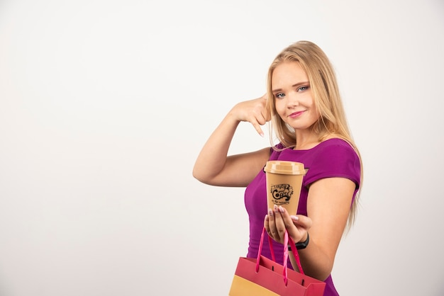 Donna elegante con tazza di caffè e borsa in posa.