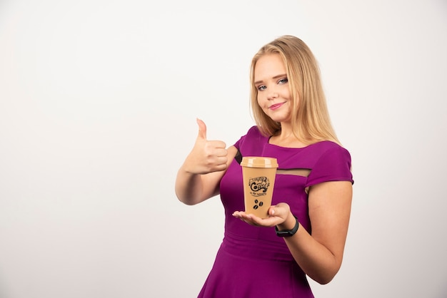 Donna elegante con una tazza di caffè in posa e che fa i pollici in su.