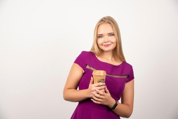 Donna elegante con la posa della tazza di caffè.
