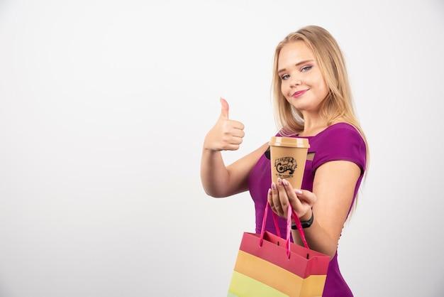 一杯のコーヒーと親指を立てるバッグを持つエレガントな女性。高品質の写真