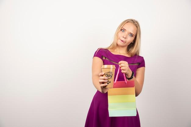 Элегантная женщина с чашкой кофе и представлять сумки.