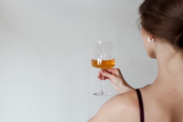 手に白ワインのグラスを持つエレガントな女性。後ろから見る。