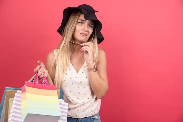 Donna elegante con cappello che tiene le sue borse della spesa e parla con il telefono.