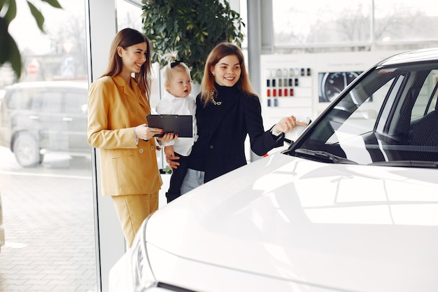 Elegant woman with little daughter in a car salon