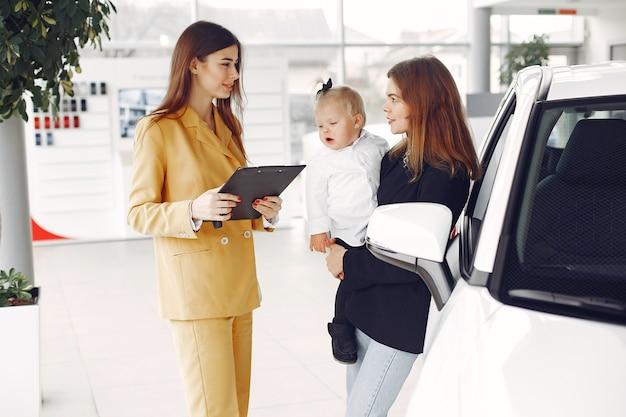 車のサロンで小さな娘とエレガントな女性