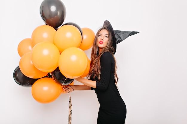 Элегантная женщина с длинными волосами позирует на белой стене на вечеринке