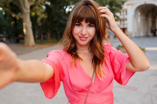 カメラでセルフポートレイトを作る完璧なウェーブのかかった髪を持つエレガントな女性。ピンクのドレスを着ています。