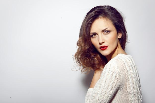 白いセーターを着て白い背景で隔離のカメラを見て赤い唇を持つエレガントな女性