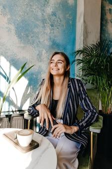 Donna elegante con capelli lunghi dritti seduti nella caffetteria. attraente ragazza europea in giacca in attesa di caffè.