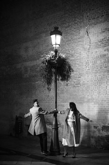 Elegant woman and young smiling man whirling near illuminated street lamp