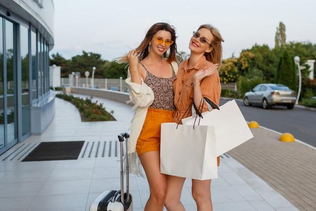 Donne eleganti dopo essere usciti dal viaggio e fare shopping in posa vicino all'aeroporto vicino