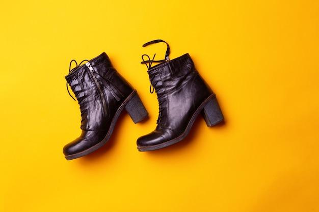 Элегантные женские черные сапоги на каблуке. вид сверху черные сапоги на желтом фоне. понятие моды и дизайна, шоппинг