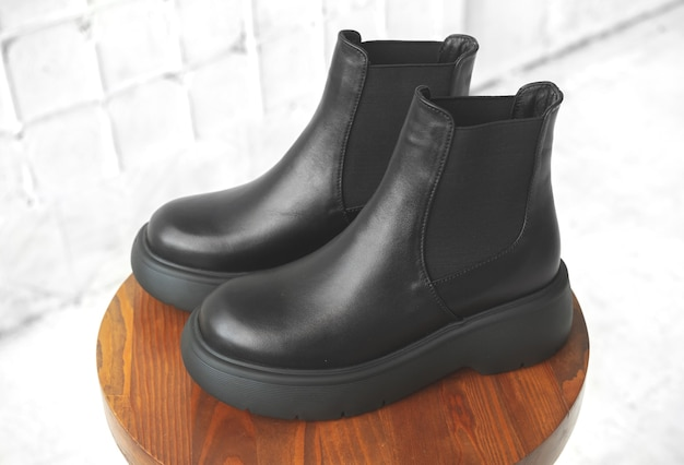 Элегантные женские сапоги. женская осенне-зимняя обувь на деревянной подставке. фото современного дизайна