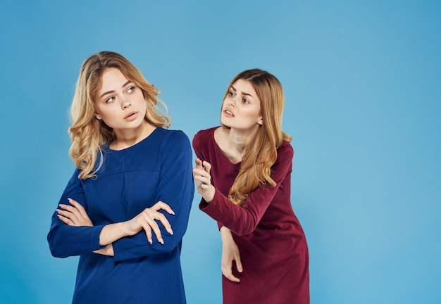 Элегантные женщины в платьях, передающие эмоции на синем фоне конфликта