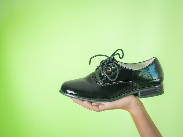 Elegant women's shoe in hand on green