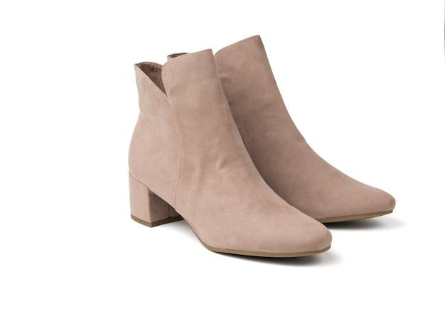 白い表面に分離されたライトベージュのスエードで作られたエレガントな女性の靴