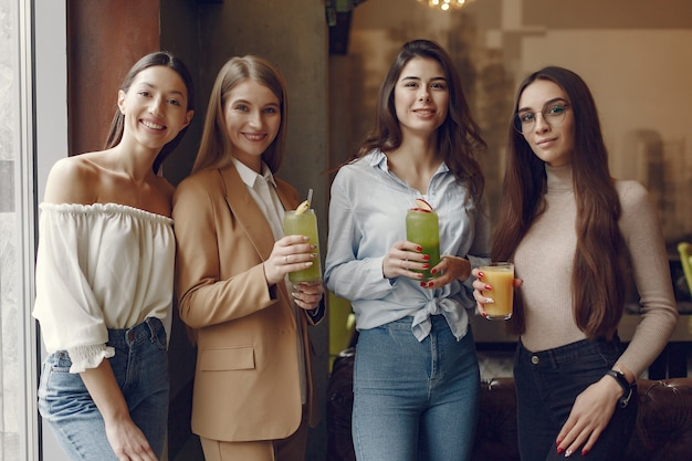 Elegant women standing in a cafe and drinking a cocktails