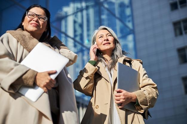 通りに立っているラップトップを持つエレガントな女性