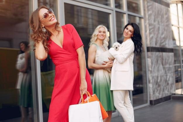 街で買い物袋を持つエレガントな女性