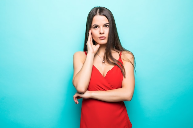 Elegant young attractive woman wearing red summer dress with hands on chin isolated over pastel blue wall.