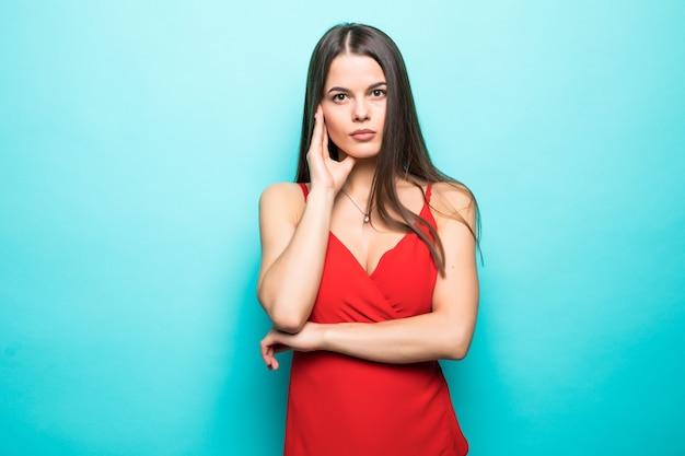 パステルブルーの壁に分離されたあごに手を赤い夏のドレスを着ているエレガントな若い魅力的な女性。