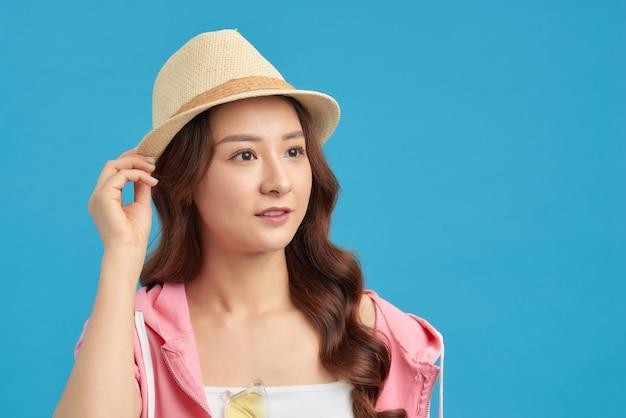 彼女の夏休みを考えて、麦わら帽子とサングラスを身に着けているエレガントな若い魅力的な女性。