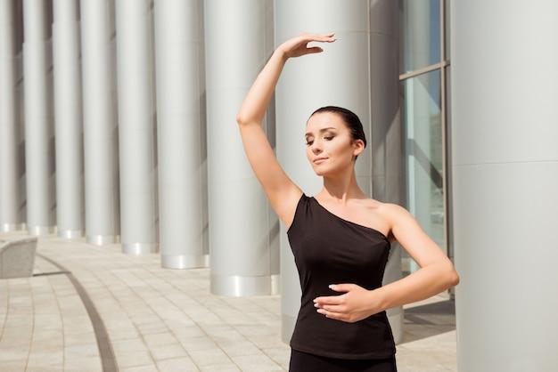Elegant young ballerina dancing in the street