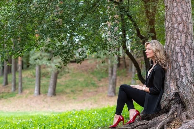 나무 옆 숲에 앉아 침묵을 즐기는 우아한 젊은 금발 아가씨