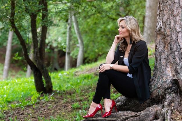 木のそばの森に座って、沈黙を楽しんでいるエレガントな若いブロンドの女性