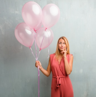 Elegant young blonde woman holding pink balloons against a wall.
