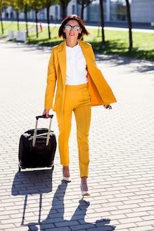 Элегантная молодая деловая женщина в стильном желтом костюме спешит на деловую встречу, разговаривает по смартфону и тянет чемодан. привлекательный бизнес женщина собирается в командировку, потянув ее чемодан.