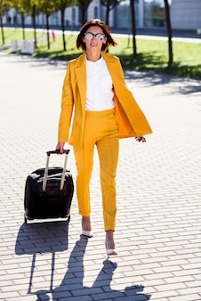 Elegant young business woman in stylish yellow suit hurries to a business meeting, talks on smartphone and pulls a suitcase. attractive business woman going on a business trip pulling her suitcase.