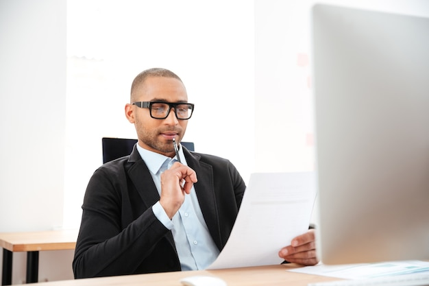 Elegant young businessman analyzing data in office