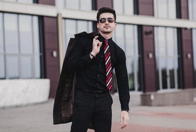フォーマルなスタイルでエレガントな青年実業家。黒のシャツとパンツ