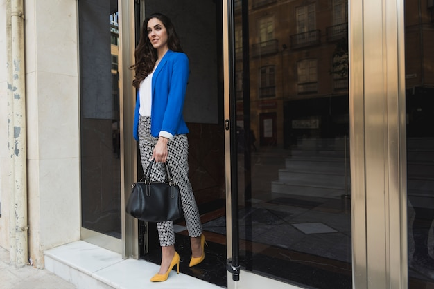 Elegant young businesswoman with blue jacket