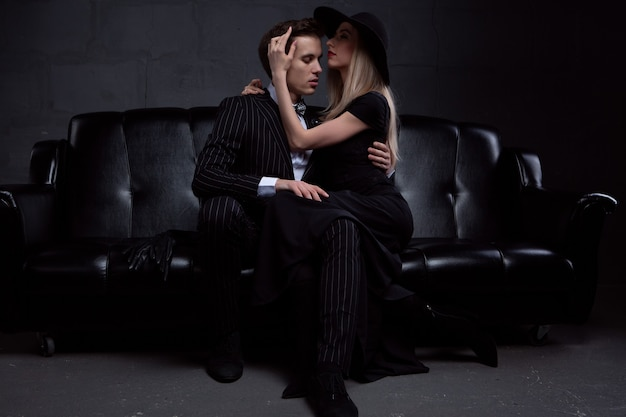 An elegant young couple in love embraces in tender passion sitting on a black leather sofa