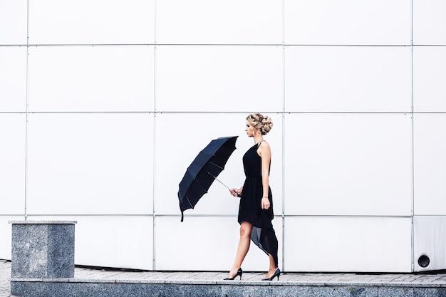 Элегантная молодая девушка в черном платье и зонтике идет по тротуару.