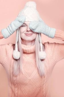 冬の帽子、暖かいセーターとミトンのエレガントな若い女の子