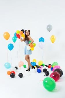 Элегантная молодая девушка позирует на модной стене после школьной вечеринки