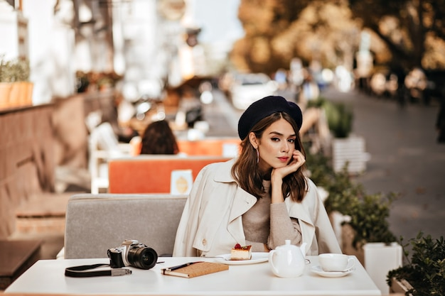 Elegant young girl with brunette wavy hairstyle, vintage beret, beige trench coat having lunch at cafe terrace in warm sunny autumn city