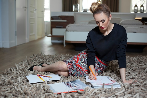 Elegant young girl with makeup and hairstyle sitting on floor sketching on paper, working at home. full length.