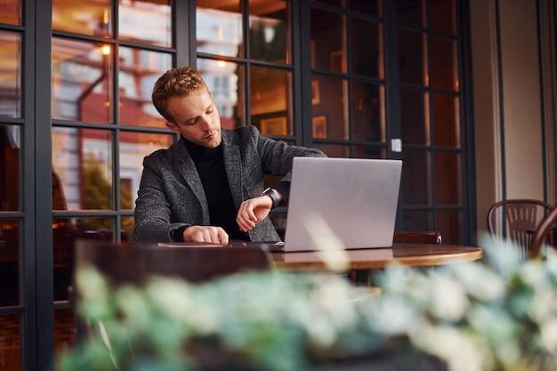 정장을 입은 우아한 젊은 남자가 노트북을 들고 카페에 앉아 시간을 확인합니다.