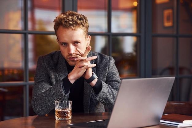 正装のエレガントな若い男は、彼のラップトップとアルコールのグラスを持ってカフェに座っています。