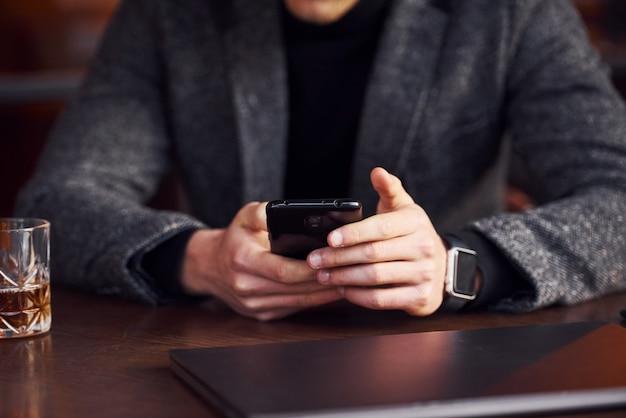 正装のエレガントな若い男は、彼のラップトップと電話を手にカフェに座っています。