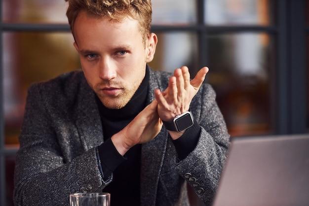 フォーマルな服装のエレガントな若い男は、彼のラップトップを持ってカフェに座っています。