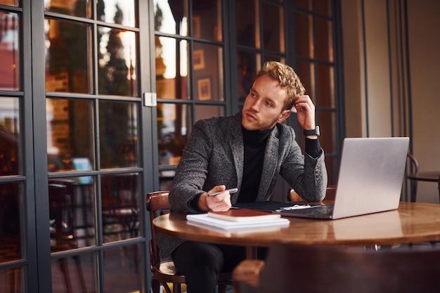 정장을 입은 우아한 젊은 남자가 노트북을 들고 카페에 앉아 있습니다.