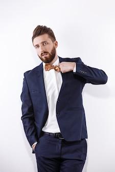 Elegant young handsome man in black classic costume studio fashion portrait