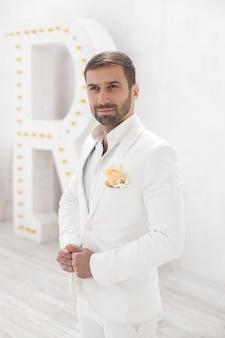 Элегантный молодой красавец с бородой в белом классическом костюме. интерьер гостиницы. фото-студия. диван. окно. стул. люстра