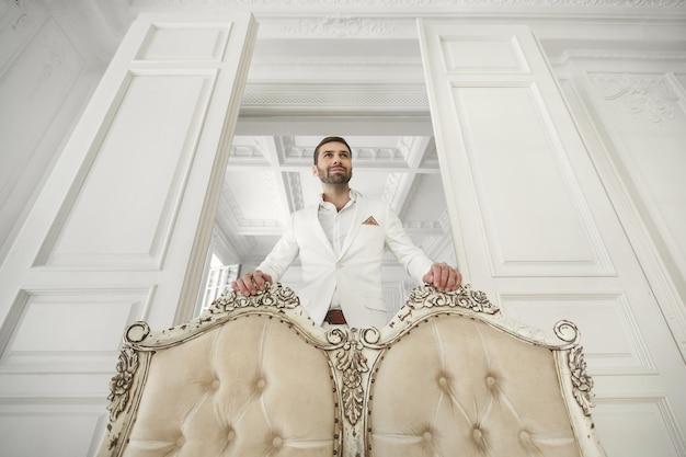 白の古典的なスーツのひげを持つエレガントな若いハンサムな男